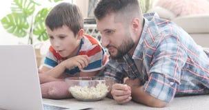 Vader en zoons het letten op media inhoud op laptop stock video