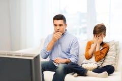 Vader en zoons het letten op verschrikkingsfilm op TV thuis Stock Foto