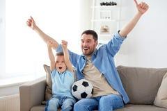 Vader en zoons het letten op voetbal op TV thuis stock foto
