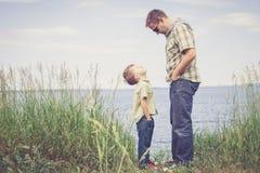 Vader en zoons het spelen bij het park dichtbij meer in de dagtijd Stock Foto's