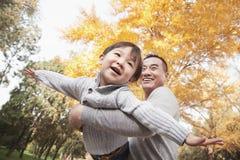 Vader en Zoons het Spelen bij Park in de Herfst stock foto's