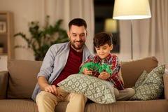 Vader en zoons het spelen met stuk speelgoed dinosaurus thuis royalty-vrije stock afbeelding