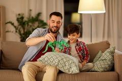 Vader en zoons het spelen met stuk speelgoed dinosaurus thuis royalty-vrije stock foto