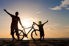 Vader en zoons het spelen op het strand in de zonsondergangtijd Stock Afbeeldingen