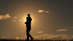 Vader en zoons het spelen in het park bij zonsondergangsilhouet van een gelukkige familie stock videobeelden
