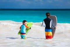 Vader en zoons het surfen Stock Afbeeldingen