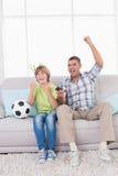 Vader en zoons het vieren succes terwijl het letten van voetbal op gelijke royalty-vrije stock foto's