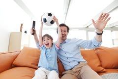 Vader en zoons wathcing voetbal Royalty-vrije Stock Afbeeldingen