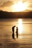 Vader en zoonsfamilie die bij zonsondergang vissen Royalty-vrije Stock Afbeelding