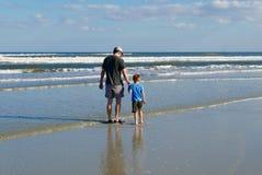 Vader en zoonsholdingshanden terwijl het lopen op het strand Stock Foto