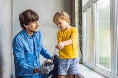 Vader en zoonsreparatievensters samen Herstel het huis zelf royalty-vrije stock foto's