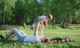 Vader en zoonsrust in het park, die pret, familie hebben Stock Foto
