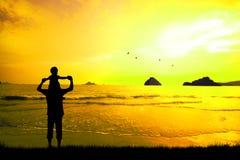Vader en zoonssilhouettenspel bij zonsondergangstrand Royalty-vrije Stock Foto's