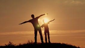 Vader en zoonssilhouettenspel bij zonsondergangstrand stock video