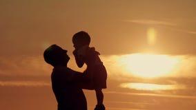 Vader en zoonssilhouettenspel bij zonsondergangstrand stock footage