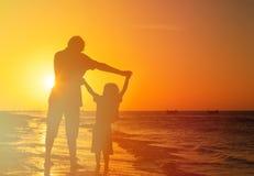 Vader en zoonsspel bij zonsondergangstrand Royalty-vrije Stock Afbeelding