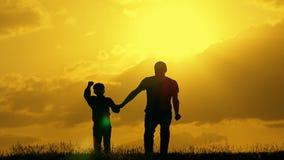 Vader en zoonsspel in het park tijdens zonsondergang Het concept een verenigde familie stock footage