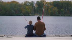 Vader en zoonsvissen op het meer stock videobeelden