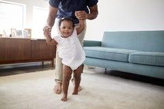 Vader Encouraging Baby Daughter om Eerste Maatregelen thuis te treffen royalty-vrije stock afbeelding