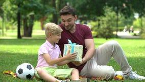 Vader geven huidig aan zoon voor goede rangen op school, moedigt om goed te bestuderen aan stock video