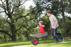 Vader Giving Son Ride in Kruiwagen royalty-vrije stock foto