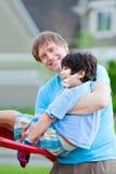 Vader helpen gehandicapt zeven van het zoonséénjarigen spel bij speelplaats Royalty-vrije Stock Fotografie