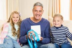 Vader het openen gift die door kinderen op bank wordt gegeven Stock Fotografie