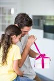 Vader het openen gift door dochter wordt gegeven die Royalty-vrije Stock Foto's