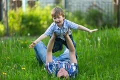 Vader het spelen met zijn kleine zoon in het gras pastime royalty-vrije stock foto