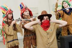 vader in hoed en bandana en kleine zonen die in inheemse kostuums met speelgoed samen spelen royalty-vrije stock fotografie