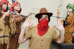 vader in hoed en bandana en kleine zonen die in inheemse kostuums met speelgoed samen spelen stock afbeeldingen