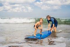 Vader of instructeur die zijn 4 éénjarigenzoon onderwijzen hoe te binnen te surfen stock fotografie
