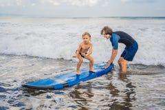 Vader of instructeur die zijn 4 éénjarigenzoon onderwijzen hoe te binnen te surfen royalty-vrije stock foto