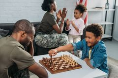 Vader in leger eenvormig het spelen schaak met zijn zoon terwijl moeder en dochter stock afbeeldingen