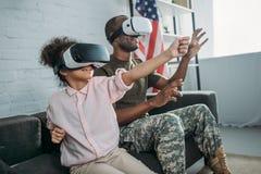 Vader in leger het eenvormige en Afrikaanse Amerikaanse dochter gebruiken royalty-vrije stock foto