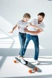 Vader leuk onderwijzen weinig dochter berijdend skateboard stock foto