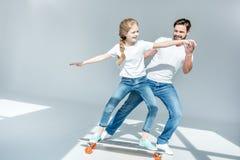 Vader leuk onderwijzen weinig dochter berijdend skateboard stock afbeelding