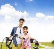 vader met dochter berijdende fiets in openlucht royalty-vrije stock fotografie