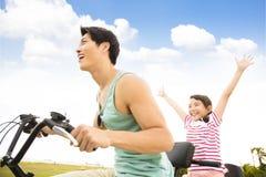 vader met dochter berijdende fiets in openlucht stock fotografie