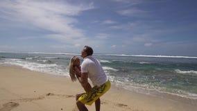 Vader met dochter met kind op het strand stock footage
