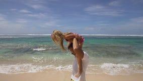 Vader met dochter met kind op het strand stock videobeelden