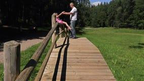 Vader met dochter op houten brug in het park stock video