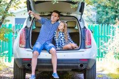 Vader met dochterzitting in een auto vlak alvorens voor een autovakantie weg te gaan royalty-vrije stock afbeelding