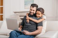 Vader met dochterzitting op bank en thuis het gebruiken van laptop Stock Afbeelding