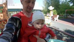 Vader met een kind op de carrousel stock footage