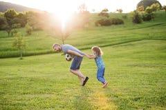 Vader met een kleine dochter die met een bal in de lenteaard bij zonsondergang spelen royalty-vrije stock foto