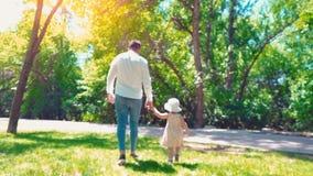 Vader met een kleine dochter die langs de groene handen van de parkholding, de achtermening, de papa en de dochter lopen stock videobeelden