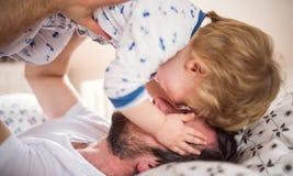 Vader met een peuterjongen die pret in slaapkamer hebben thuis bij bedtijd royalty-vrije stock afbeeldingen