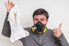 Vader met gasmasker die stinkende luier veranderen Stock Afbeeldingen