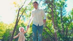 Vader met het kleine dochter lopen in de holdingshanden van het de zomerpark direct op camera, meisje die camera bekijken stock video